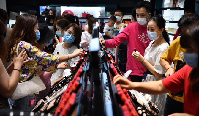 Tourists shop at a duty-free shopping mall in Sanya City, south China's Hainan Province, Oct. 5, 2020. China's gross domestic product (GDP) exceeded the 100-trillion-yuan (15.42 trillion U.S. dollars) threshold as it posted a 2.3 percent year-on-year expansion to 101.5986 trillion yuan in 2020, data from the National Bureau of Statistics showed Monday. (Xinhua/Guo Cheng)